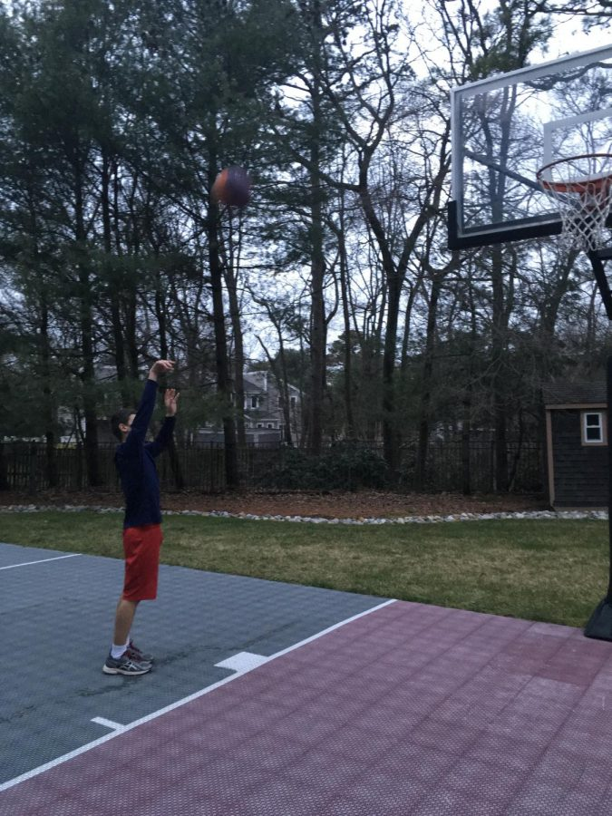 Arnstein shoots hoops on a cloudy spring day in his neighbors' backyard.