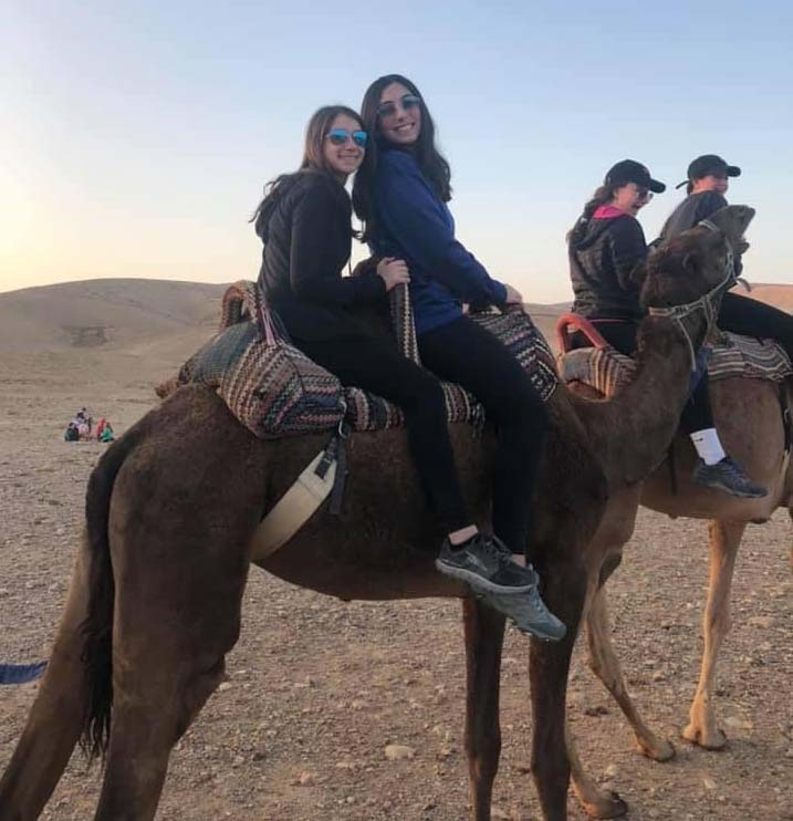 Leah rides on the back of a camel with her friend in Israel.